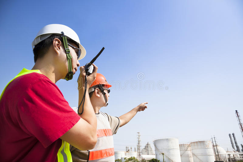 Refinery workers looking refinery. Two refinery workers looking the large refinery background royalty free stock photography