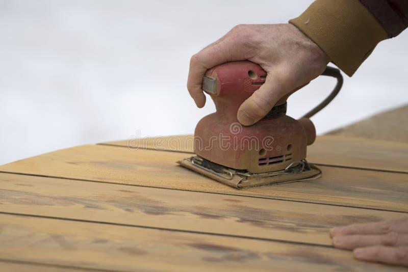 Refinishing en utomhus- cederträtabell med gömma i handflatan slipmaskinen royaltyfria bilder