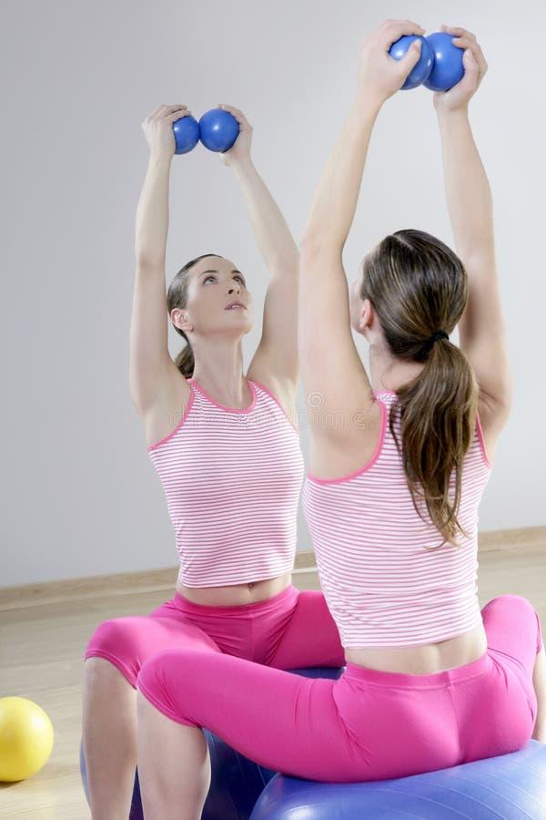 Reflétez la femme de gymnastique de pilates modifiant la tonalité la gymnastique de sport de billes image libre de droits