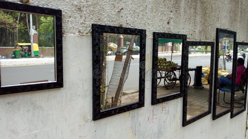 Reflaction av bilder på spegeln som hänger på en vägsidovägg, Vadodara, Indien arkivfoton