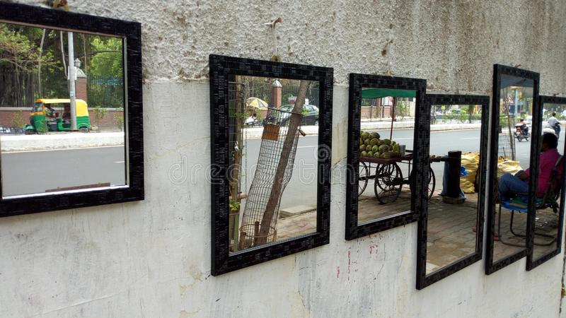 Reflaction of images on the mirror hanging on a road side wall, Vadodara, India. Reflaction of images on the mirror hanging on a   wall, vadodara, roadside stock photos