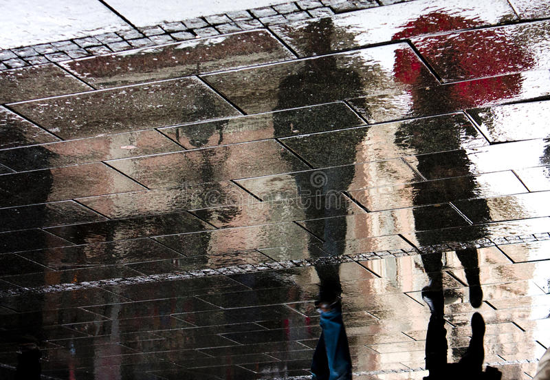 Reflected shadows on a rainy day. Reflection shadow of a couple walking in the rain in the city pedestrian zone royalty free stock photos