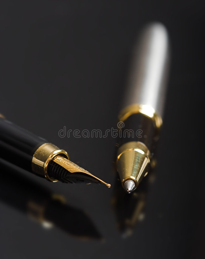 Reflected writing. Pen and ballpoint reflected on a shiny surface royalty free stock photography