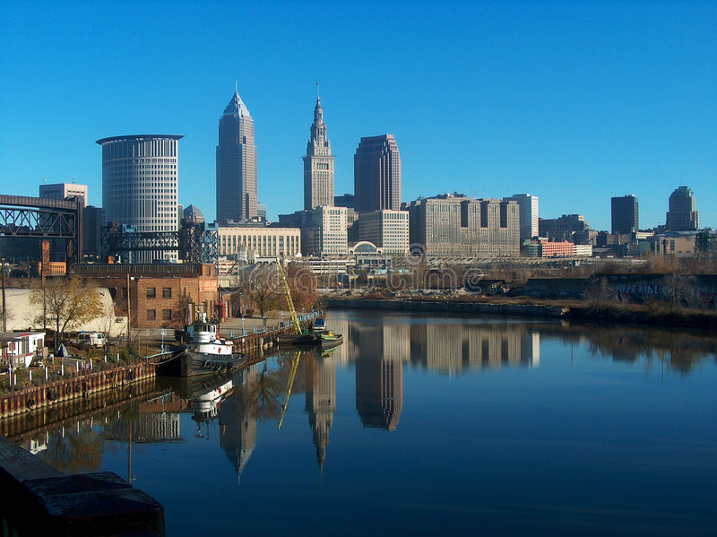 Reflecting Cleveland Skyline. The Cleveland Ohio skyline reflecting off of the Cuyahoga river beneath a beautiful clear blue sky