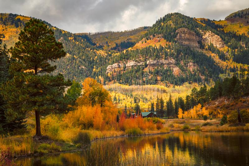 Reflecting on days passed. A small cottage on a lake in the Colorado San Juan Mountains in the fall stock photo