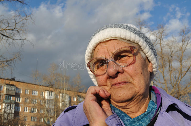 Reflecting an elderly woman wearing glasses stock photo