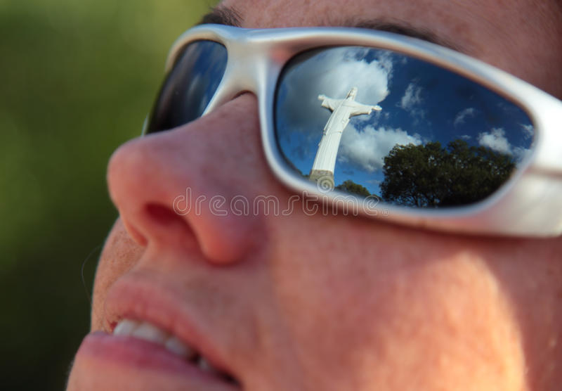 Reflecting on Faith. A reflection of a statue of Jesus in a gir's sunglasses stock photography