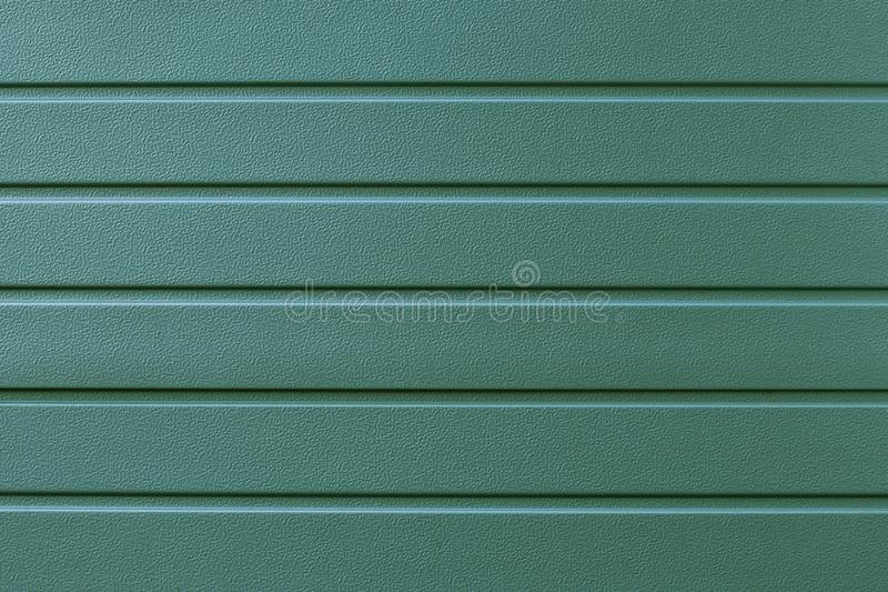 Reflecting metal convex texture in lines. Green metallic ribbed surface. Abstract pattern. Metal shutters backdrop. Green backgrou. Nd of steel plate. Metalline royalty free stock photos