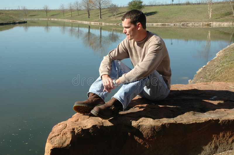 Reflection. A man in casual clothing sits alone on a rock by a pond. Man sitting in a park or nature park. Man being thoughtful: occupied with or given to royalty free stock image