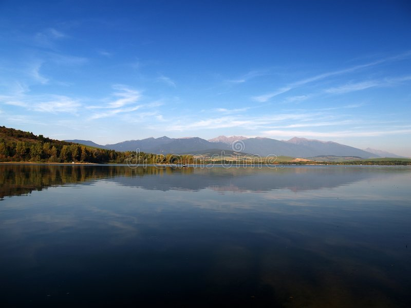 Reflection. Of mountains in deep lake stock photography