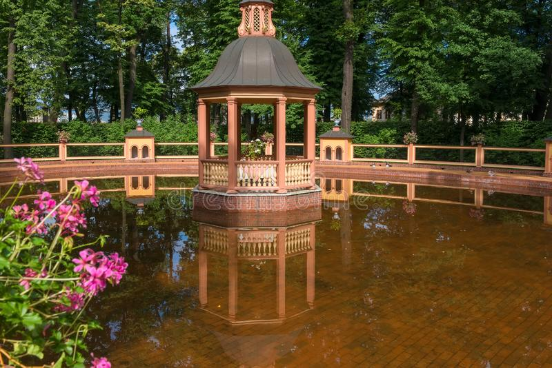 Reflection of the arbor in the water of the pond. SAINT PETERSBURG, RUSSIA - AUGUST 18, 2017: Bosket `Menagerie pond` 1720, according to the drawings of Jan stock images