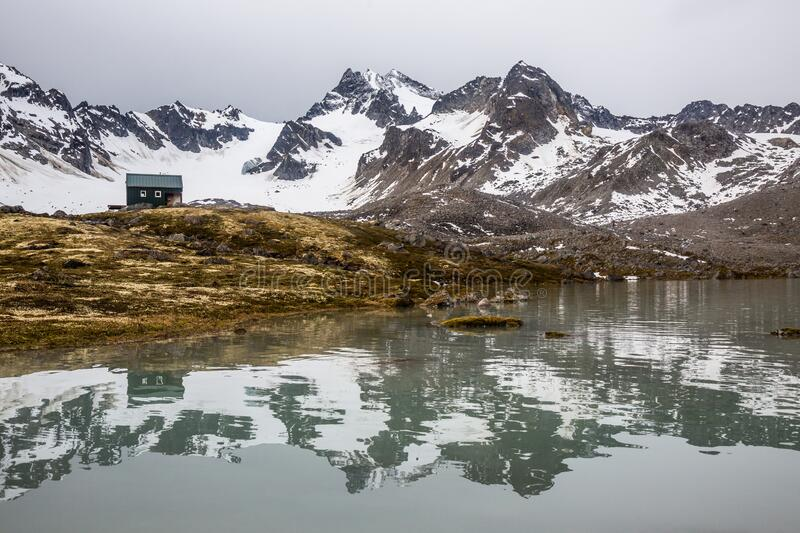 Reflection of a backcountry shelter in remote Alaska. Small green backcountry hut in remote Alaska, reflected in a calm alpine lake in the Talkeetna Mountains royalty free stock photos