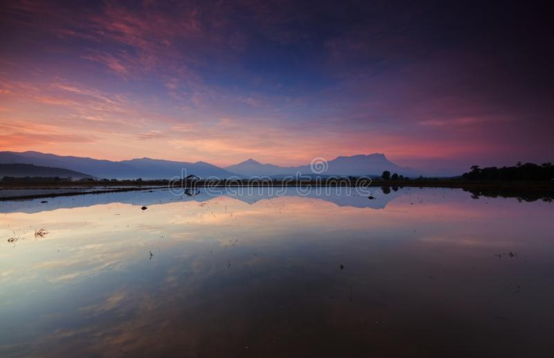 Reflection of beautiful sunrise at Kota Belud, Sabah stock photography