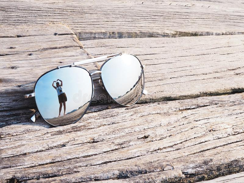 Reflection of blue sky and clouds heart shape in sunglasses stock photo