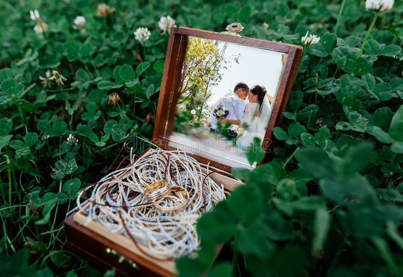 Reflection of the bride and groom in the mirror of wooden box with golden wedding ring stock image