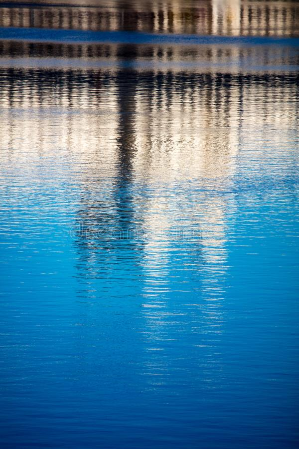 Reflection of a building on the smooth surface of water as a background stock images