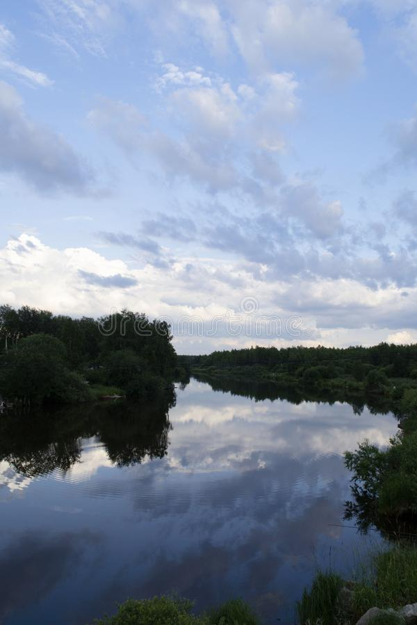 Reflection of a cloudy sky in the water. Iset river. Ural, Sverdlovsk region, Russia royalty free stock image