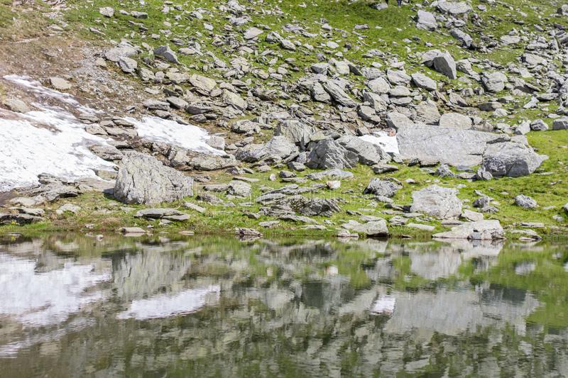 Reflection of the coast in water of a mountain lake stock photos