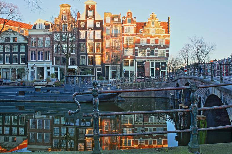 Reflection of crooked and colorful heritage buildings along Prinsengracht Canal and next to Brouwersgracht Canal. With Lekkeresluis Bridge on the right royalty free stock image