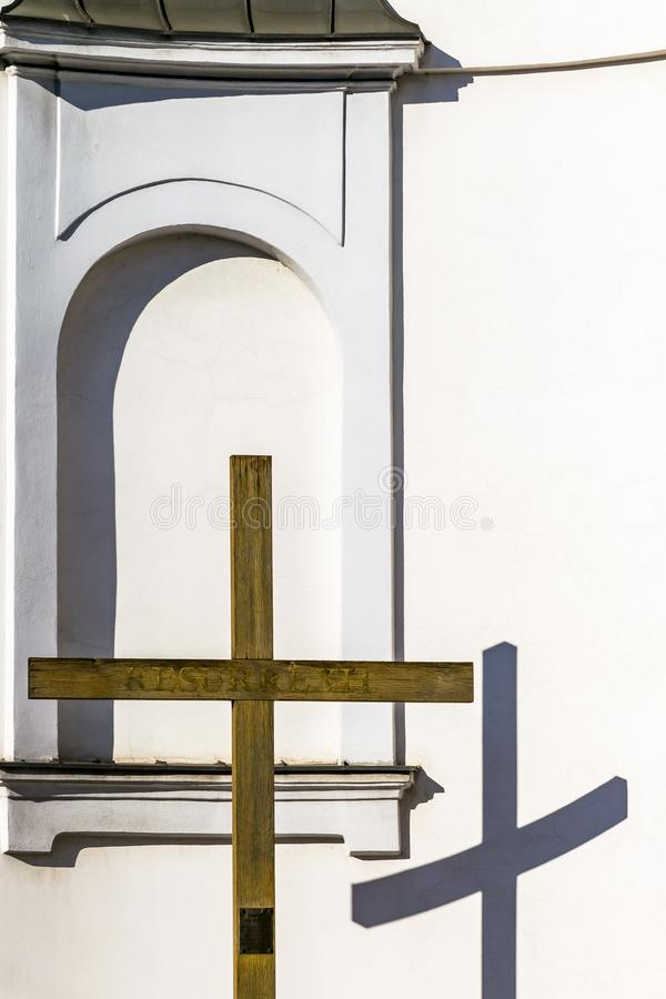 Wooden cross and church wall, Christian religious theme. Reflection of cross on wall of Catholic church on sunny day royalty free stock photography