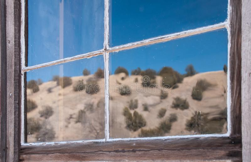 Reflection of desert in window of abandoned building, ghost town Chloride NM. Horizontal reflection of desert scene in the window of an abandoned building in the royalty free stock image