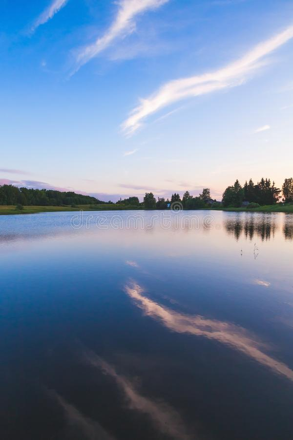 Reflection of evening cloudy sky in still lake stock photo