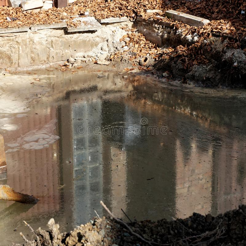 Reflection in an excavation pit with groundwater on which a thick, greasy layer of heating oil floats. Germany royalty free stock photography
