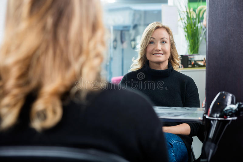 Reflection Of Female Customer Smiling In Salon. Reflection of mature female customer smiling in beauty salon stock images