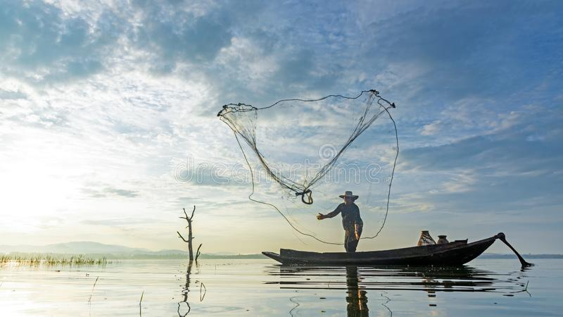 Reflection fisherman action when fishing net with dry alone tree on the boat in the lake outdoors, royalty free stock photo