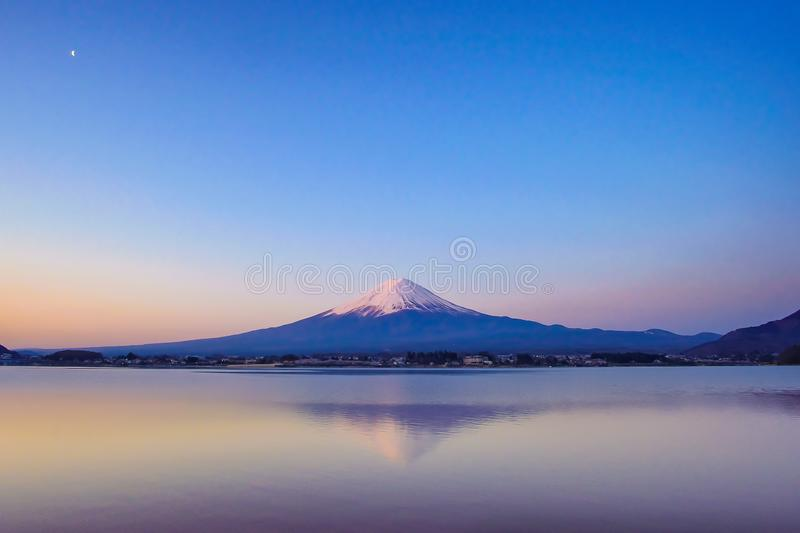 Reflection of Fuji mountain with snow capped and the Moon in the morning Sunrise at Lake kawaguchiko, Yamanashi, Japan. Landmark and popular for tourist royalty free stock photography
