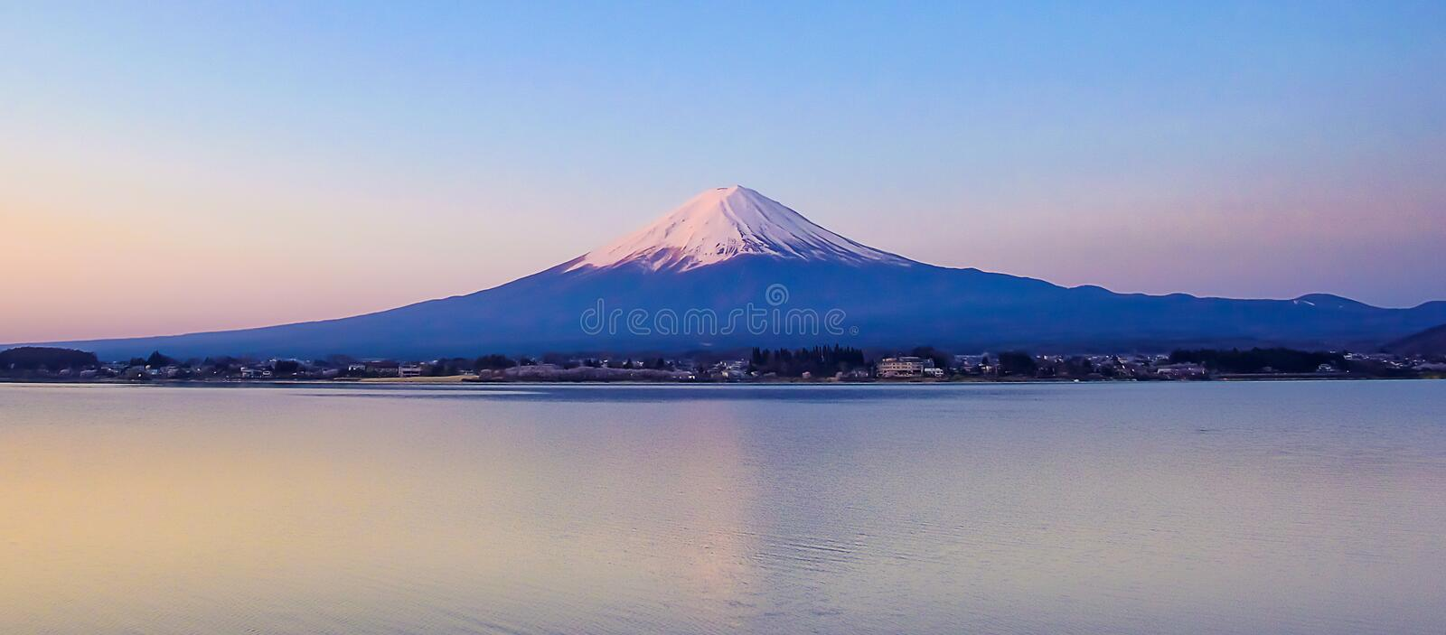 Reflection of Fuji mountain with snow capped and the Moon in the morning Sunrise at Lake kawaguchiko, Yamanashi, Japan. Reflection of Fuji mountain with snow stock photography