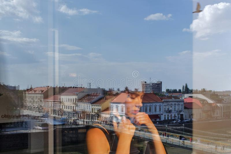 Reflection of a girl in the window on the background of the ancient city stock photography