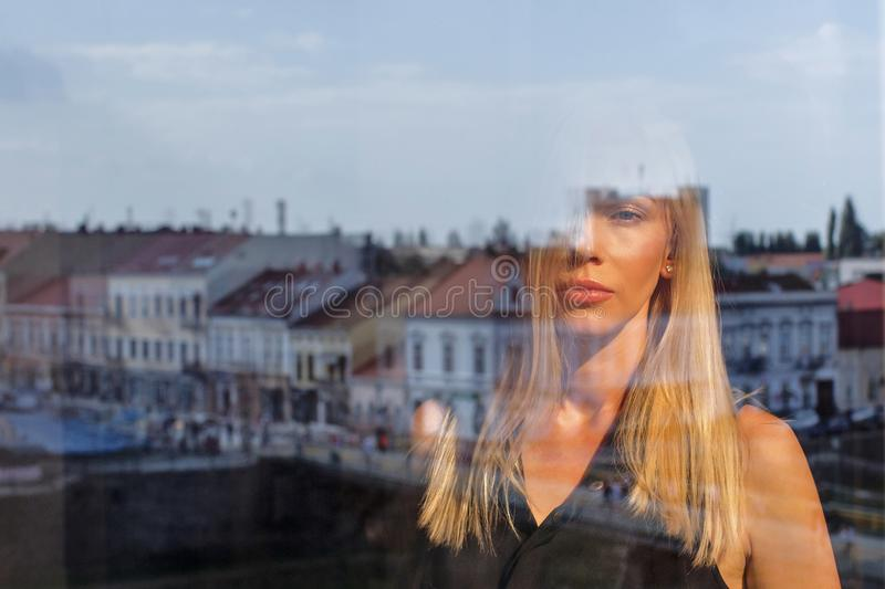 Reflection of a girl in the window on the background of the ancient city royalty free stock photo
