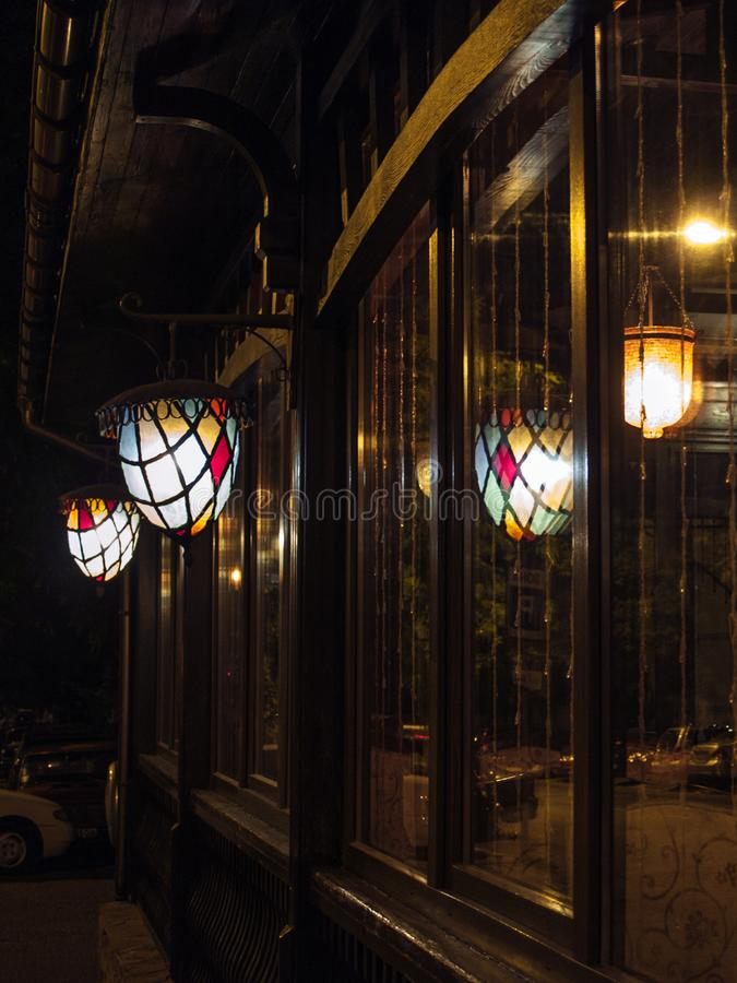 Reflection in the glass, on the street, night, multicolored, cast iron lanterns royalty free stock image