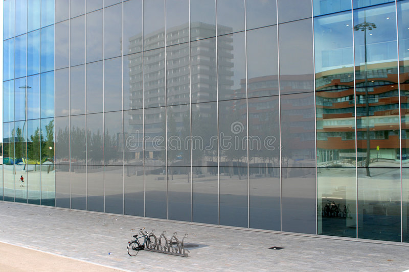 Reflection in glass wall. A skyscraper and other buildings are reflecting in the enormous glass wall of a modern building in Almere in the Netherlands; in front royalty free stock photo