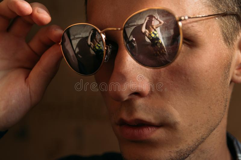 Reflection in the glasses of a beautiful girl.portrait of a beautiful young man in sunglasses, which reflects a beautiful girl royalty free stock photos