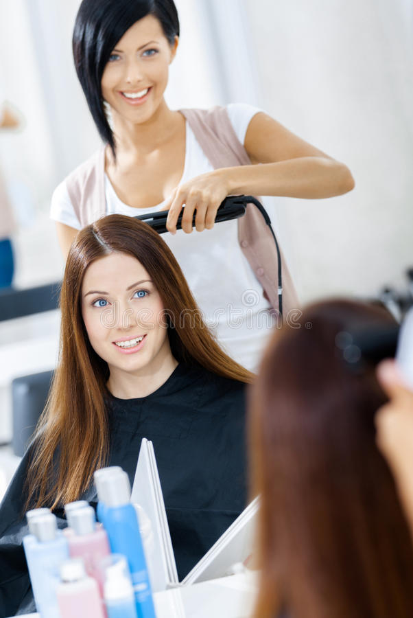 Reflection of hair stylist doing haircut for woman stock photography