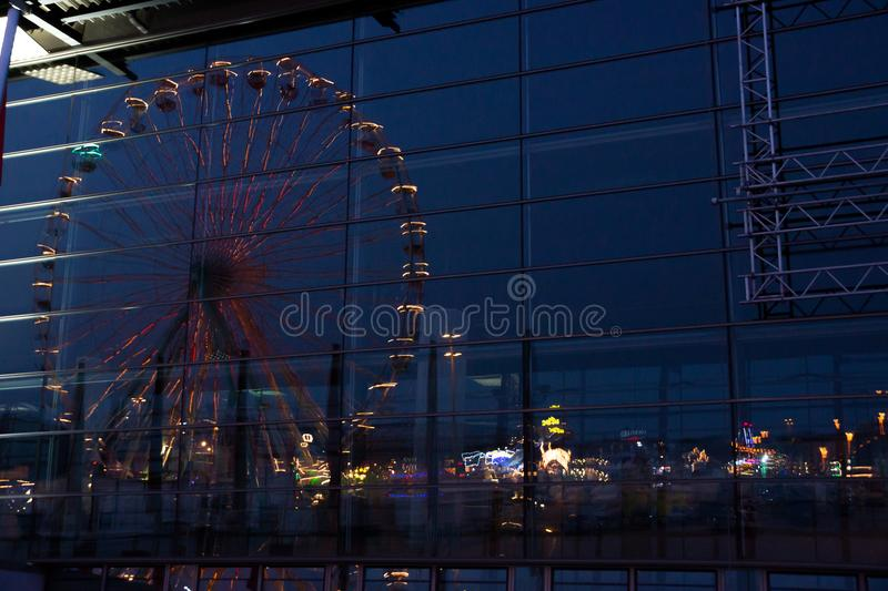 Reflection of an illumiated large ferris wheel in large hall windows royalty free stock images