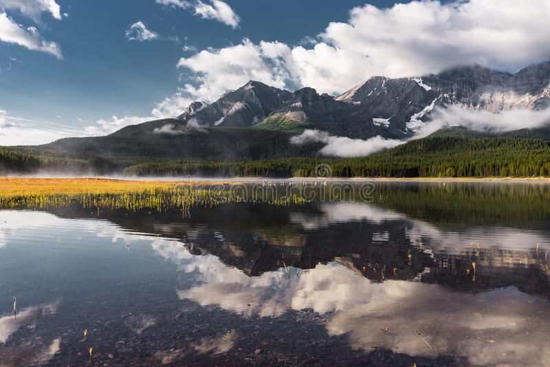 Reflection with lake and mountains low hanging couds in Lower Kananaskis Lake of Peter Lougheed Provincial Park stock image