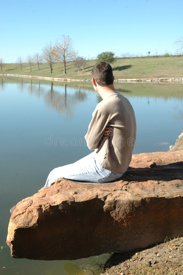 Reflection of Life. A man in casual clothing sits alone on a rock by a pond. Man sitting in a park or nature park. Man being thoughtful: occupied with or given stock image