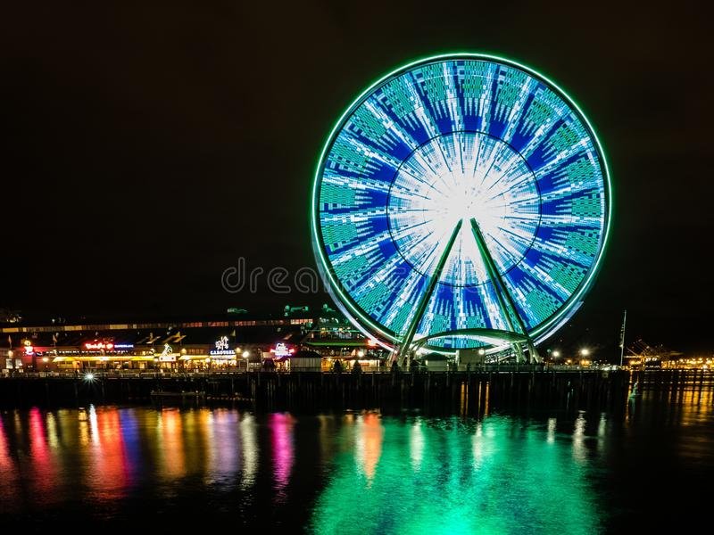 Reflection of the lights on the Ferris Wheel on the coastline of Seattle, USA at night. The reflection of the lights on the Ferris Wheel on the coastline of stock images