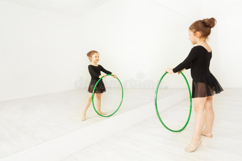 Reflection of little gymnast with hula hoop. Reflection of five years old girl in black dancewear practicing gymnastic with hula hoop in well lit dance hall stock photo