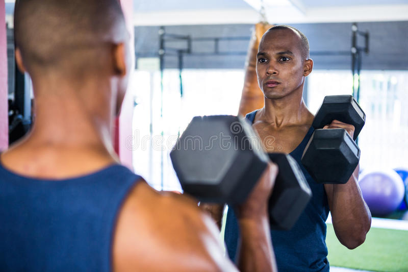 Reflection of male athlete exercising with dumbbell. On mirror in gym royalty free stock photography