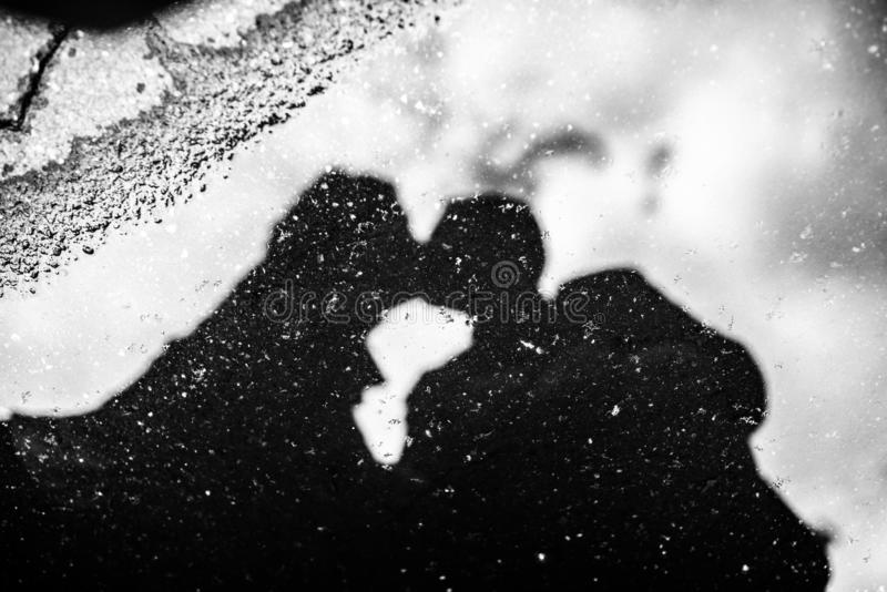 Reflection of a man and woman in a puddle stock images