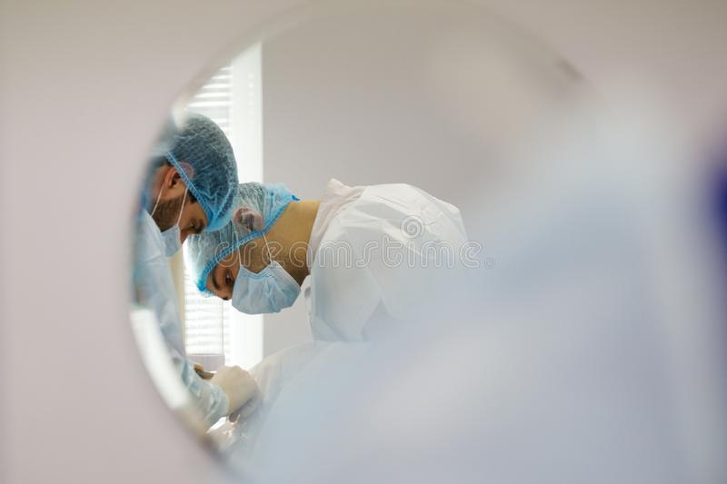 Reflection in the mirror - Doctor dentist and assistant during stomatology operation royalty free stock photography
