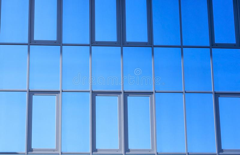 Glass mirror. Reflection in a mirror glass of a building of a blue sky, close-up of a part of a modern building royalty free stock photo
