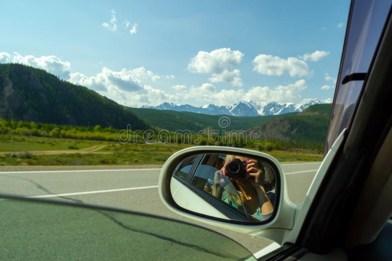 Reflection in the mirror of a riding white car of photographer w royalty free stock photo