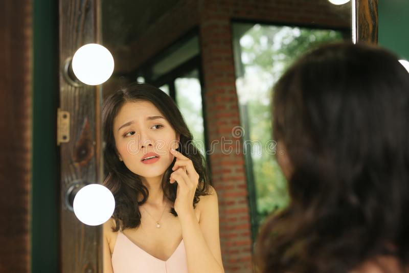Reflection in the mirror. Woman looks in the mirror noticing the first wrinkles.  royalty free stock photography