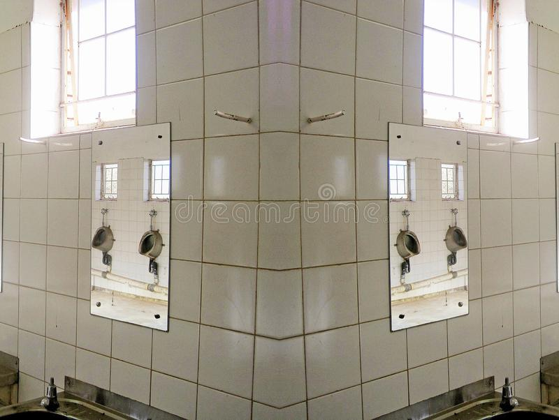 REFLECTION OF MIRRORED URINALS. View of a duplication of a bathroom in a deteriorated state showing signs of ruin and decay stock photography