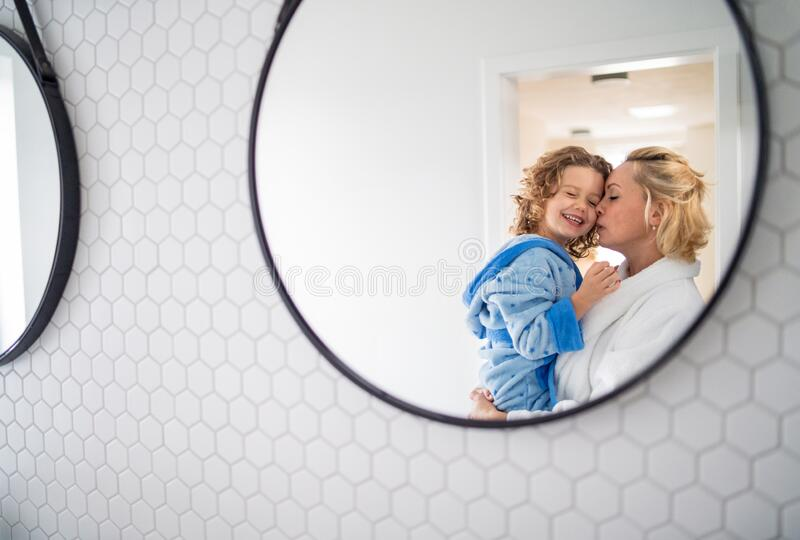 A reflection of mother and small daughter in mirror in bathroom. royalty free stock image